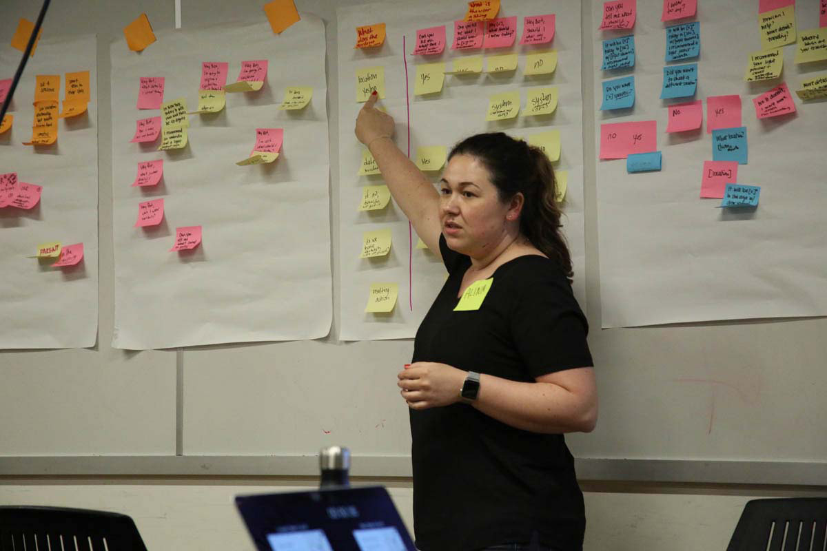 a woman giving a talk while pointing to a wall of post-its