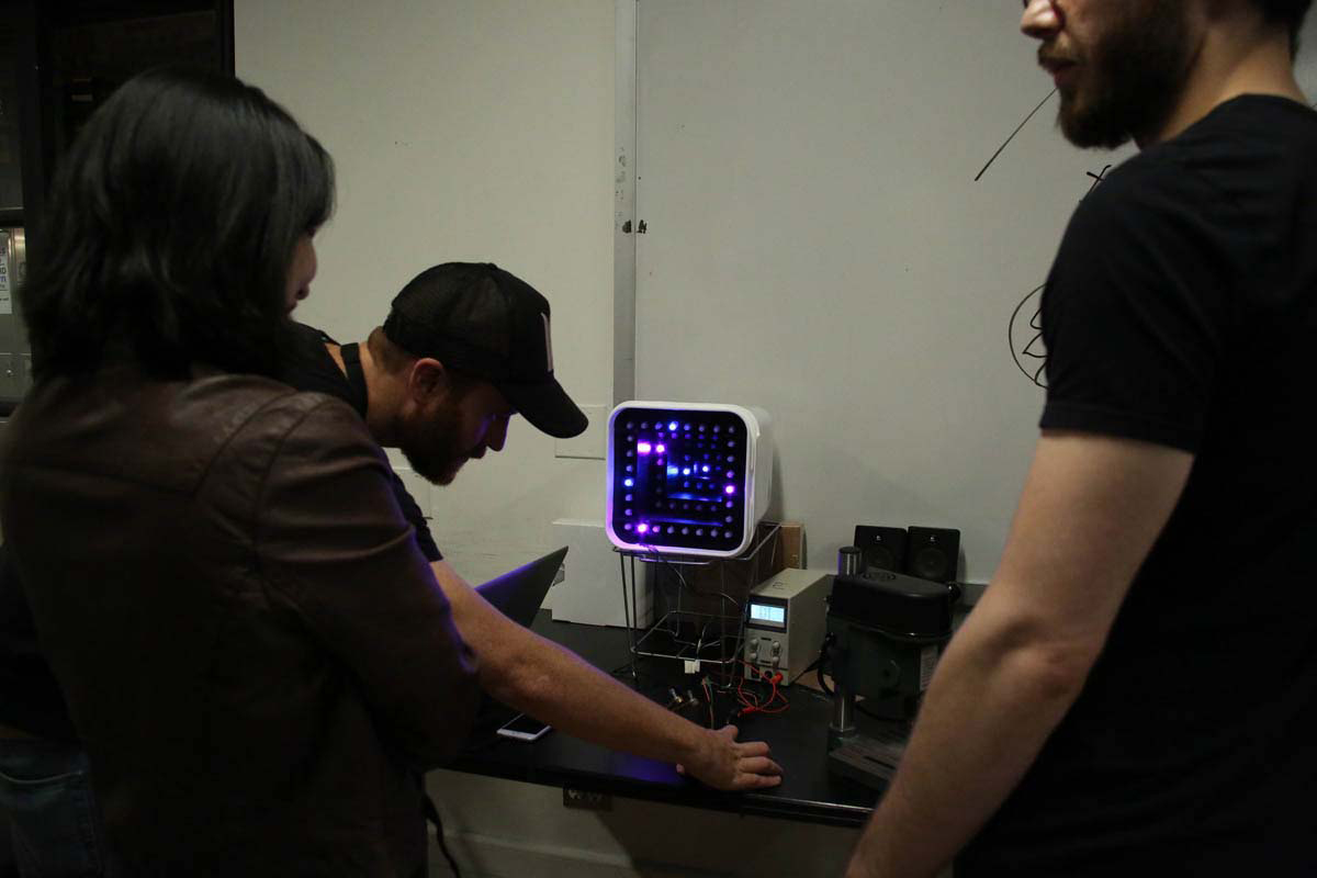a person working with a monitor that is lit up by LED's