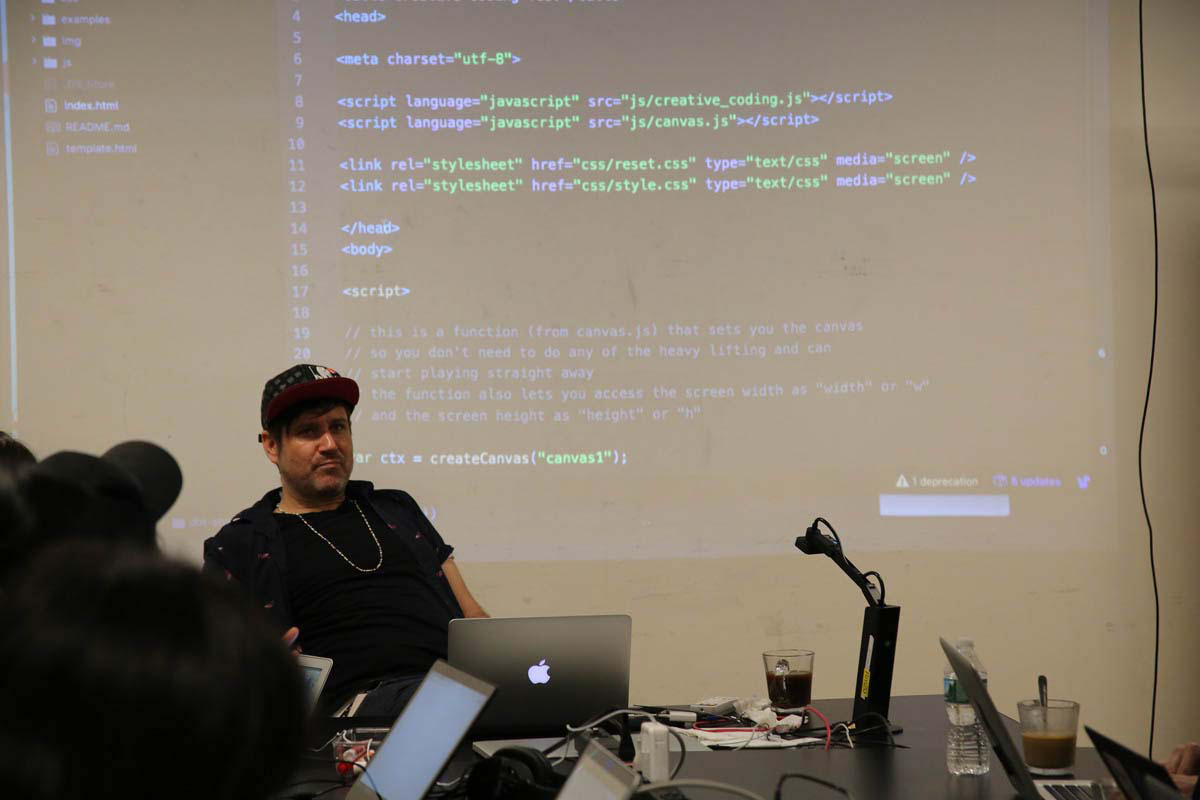a man giving a lecture with code in the background