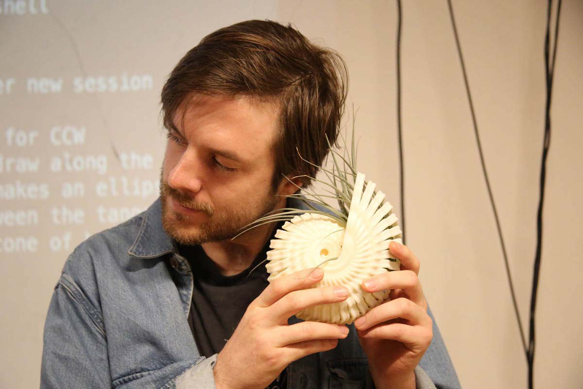 a man holding a spiral shell with leaves coming out