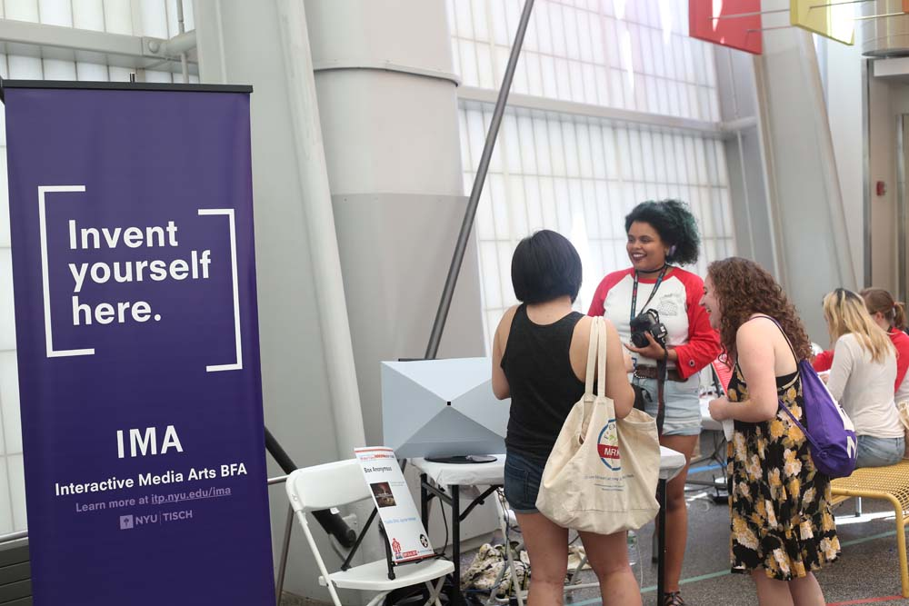 A woman talking to 2 people with the IMA banner in the foreground