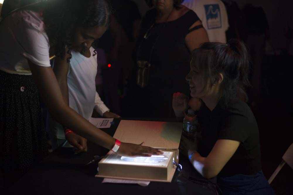 A person places their hand on a light up box