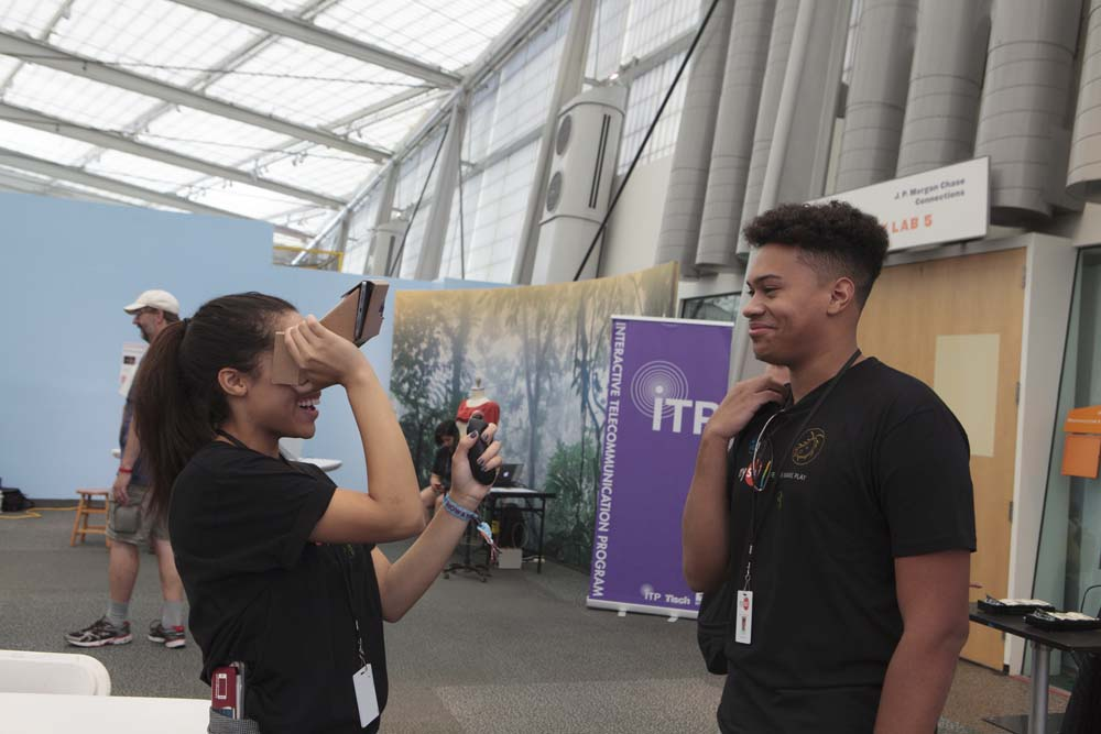 A woman using Google Cardboard while a man looks on smiling