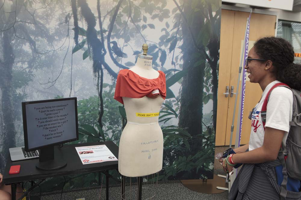 A person smiling as they look at a mannequin with a blouse and fake chattering teeth appearing from under the shirt