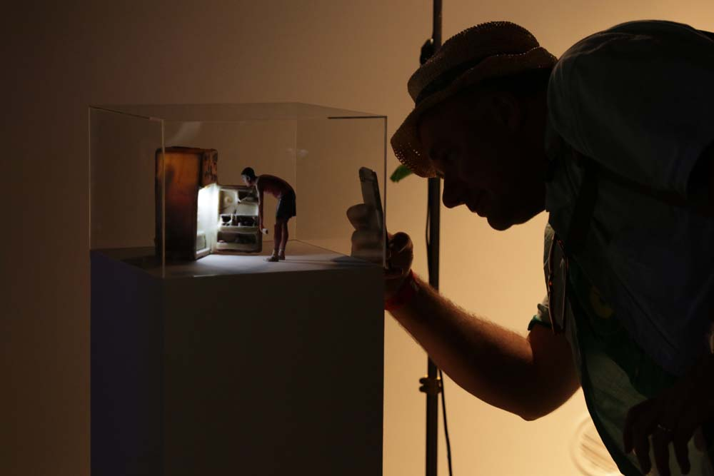 A miniature sculpture of a person looking into a fridge, while a person takes a photo of it