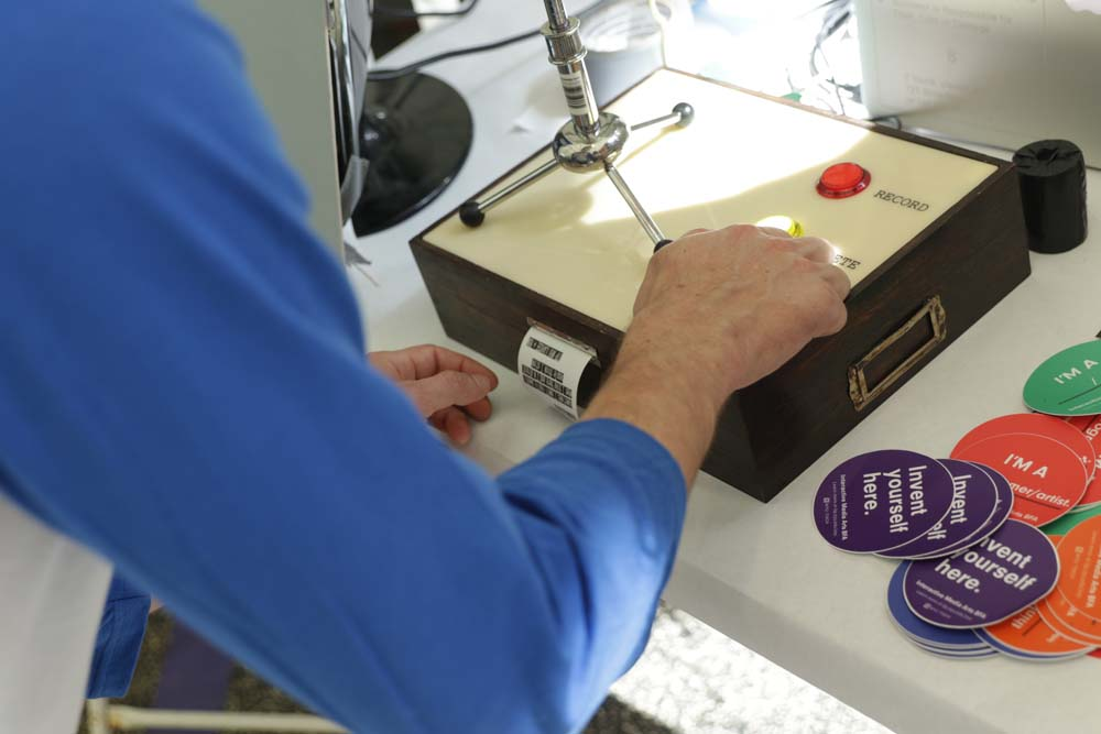 A hand pressing buttons on a box with a receipt being printed