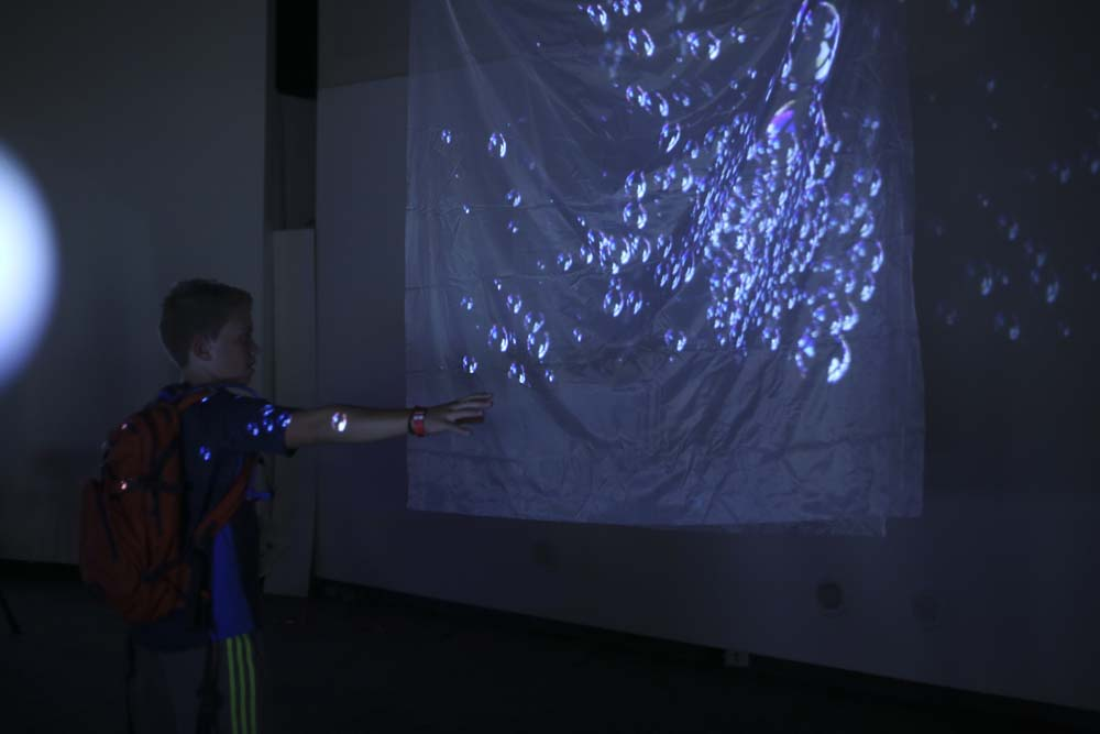 a boy interacting with a projection of bubbles