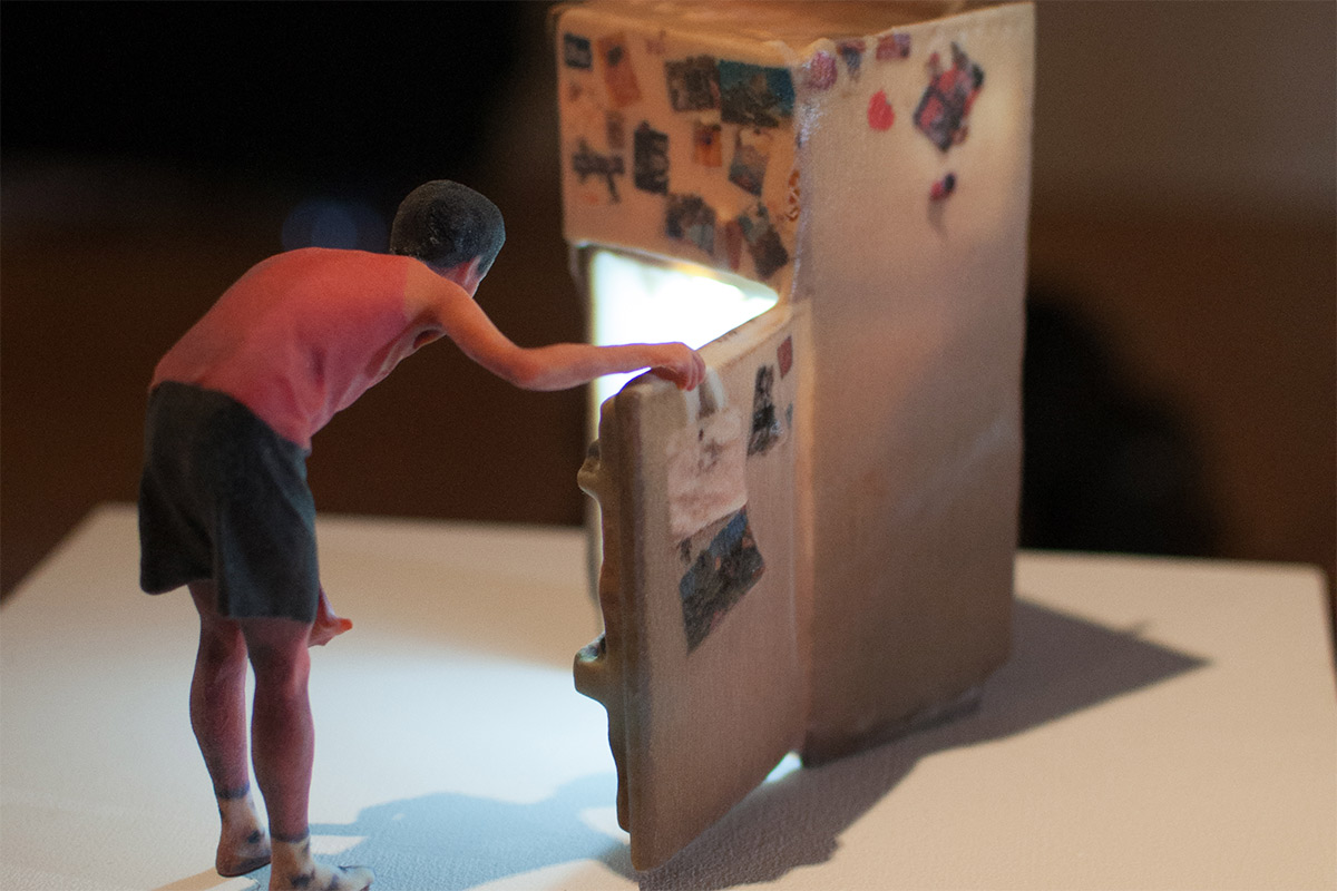 a miniature sculpture of a person looking inside a refrigerator