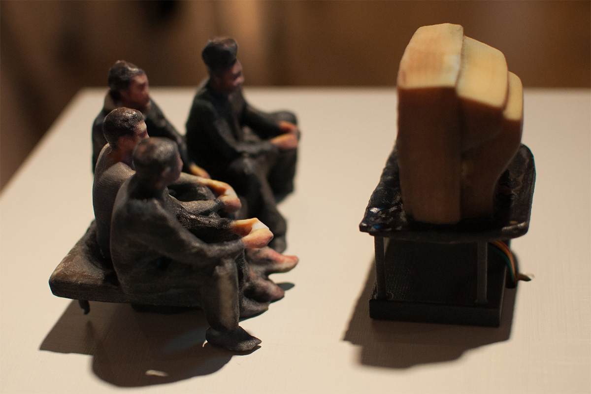 a miniature sculpture of a group of people watching TV