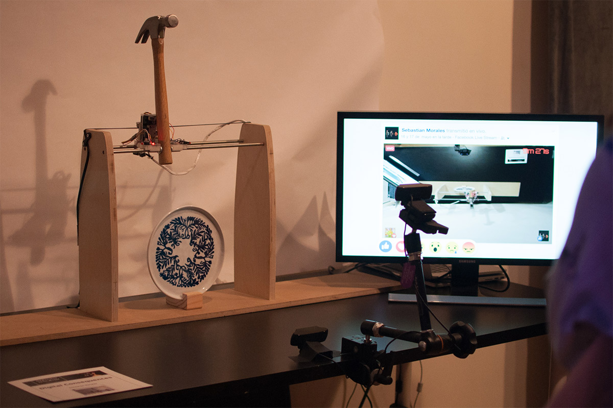A hammer propped up, ready to swing down and break a plate, next to a monitor