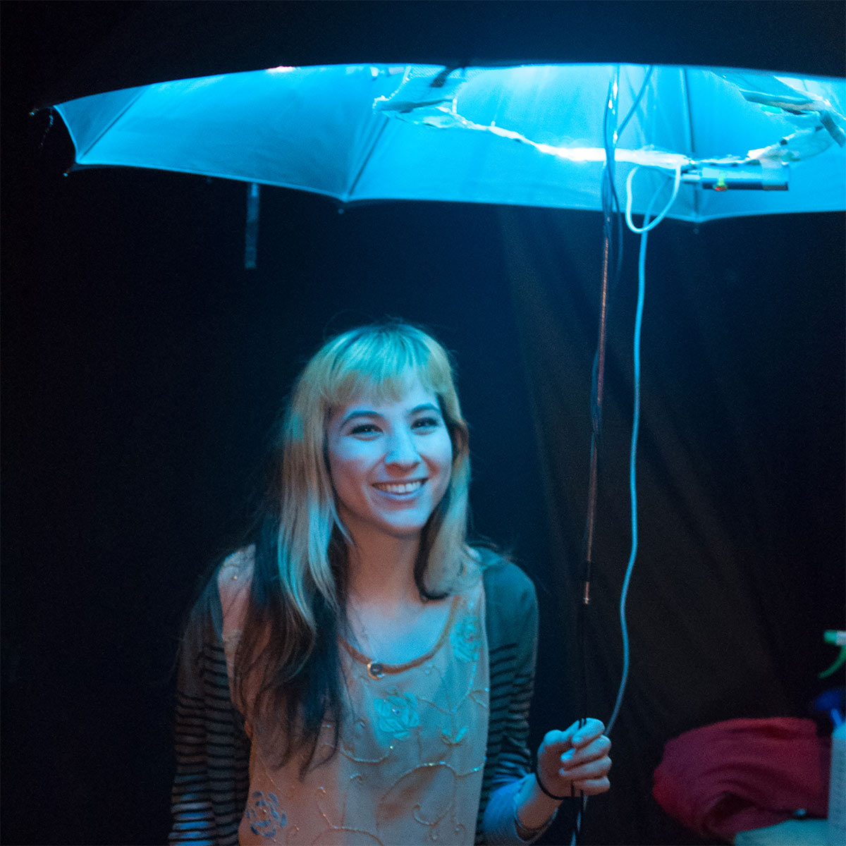 a woman holding an umbrella with lights illuminating it from within