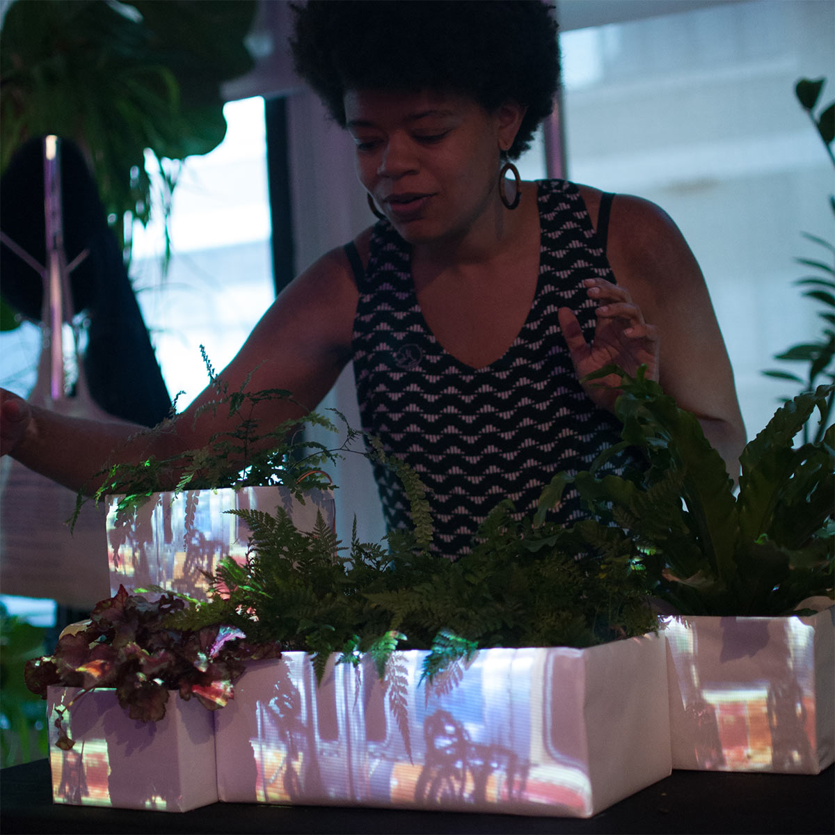 a woman with potted plants with projections on the pots