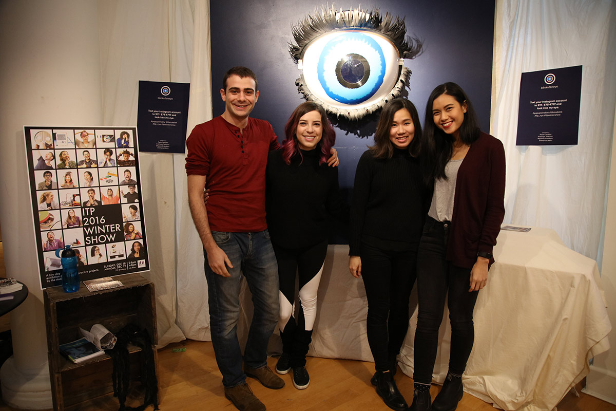 4 students smiling with a gigantic eye sculpture behind them