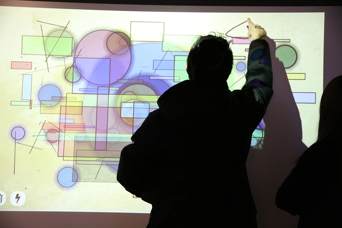 a projection of shapes of different colors and a person drawing his own shape