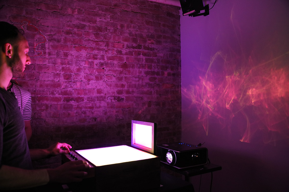 a person interacting with a screen projecting an ethereal shape on the screen