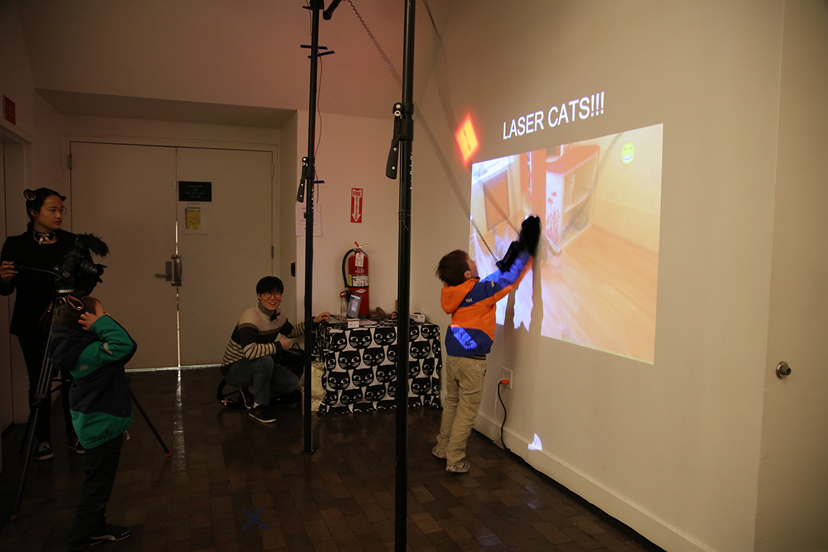a boy wearing a glove interacting with a cat projected on the wall