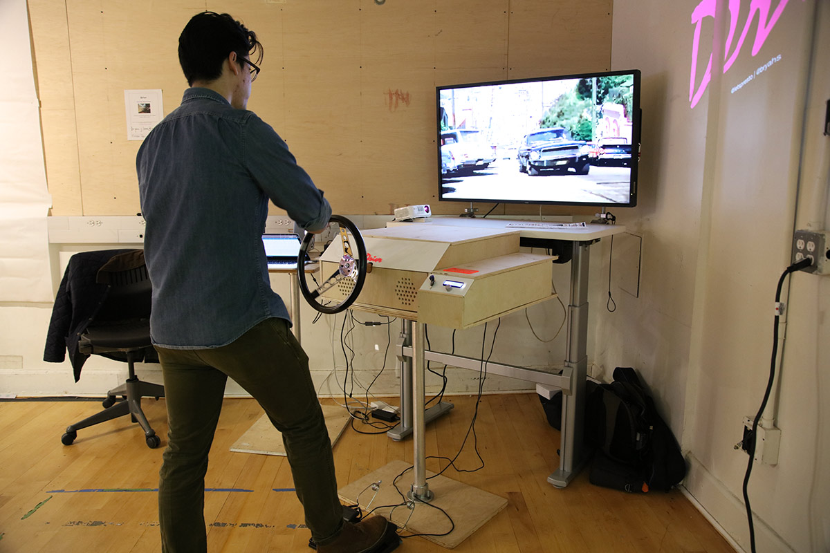 a person driving a simulated car while watching footage on a flat panel screen