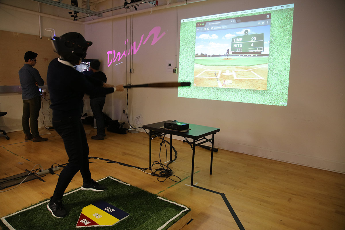 a person wearing baseball helmet and bat hitting a virtual pitch