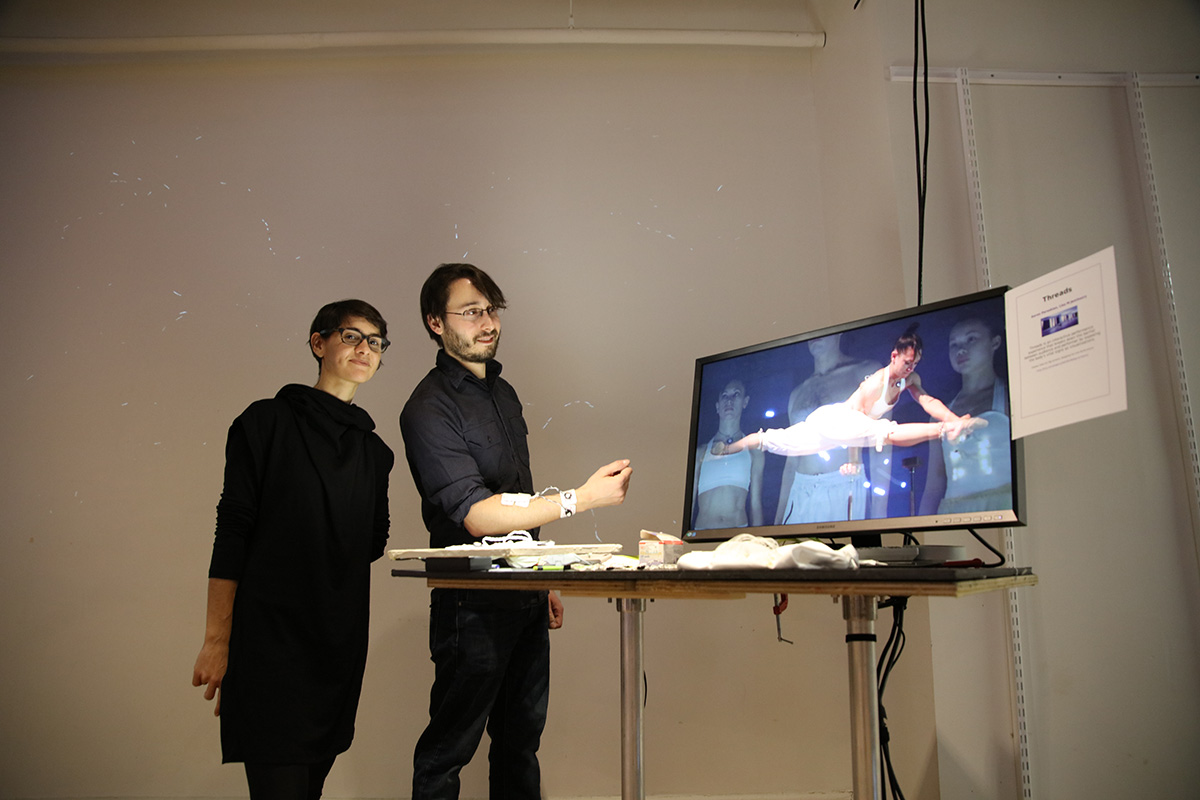 Two people standing next to a monitor showing a dancer doing the splits