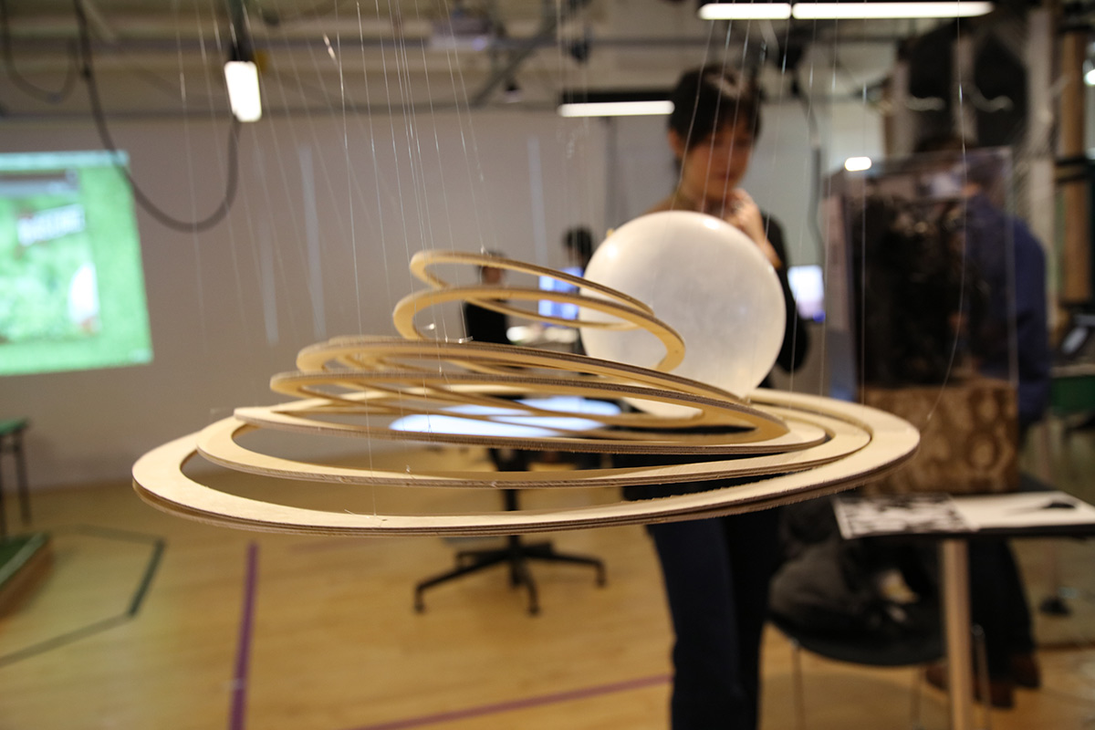 Wooden concentric circles suspended in air with a ball rolling on top