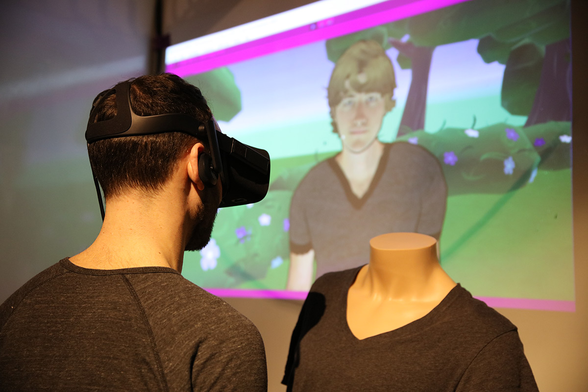 A man wearing VR googles standing next to a headless mannequin with a computer generated image of a person projected