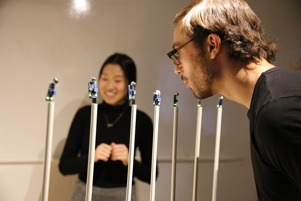 a person blowing into sensors on sticks