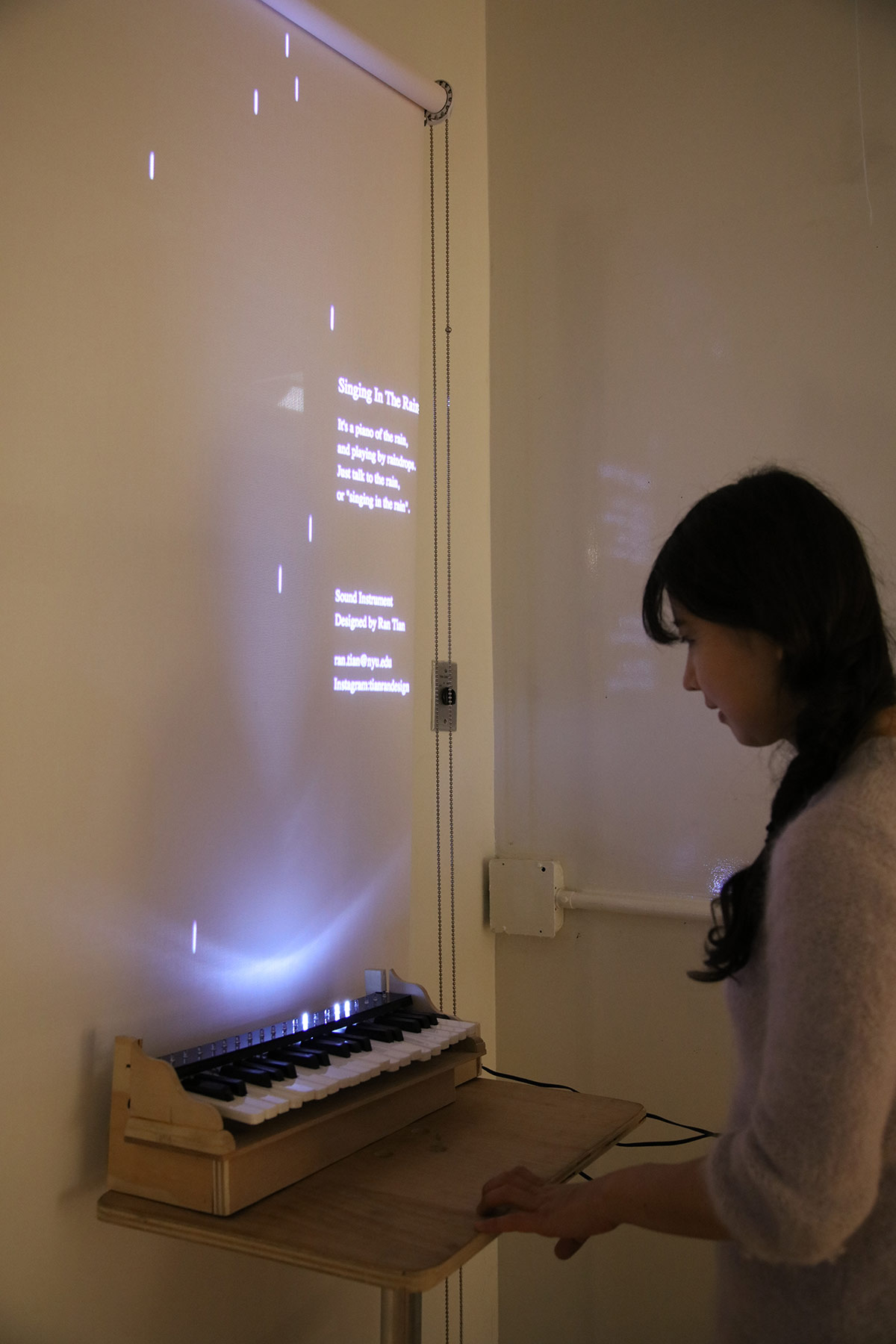 a woman standing in front of a small keyboard that is triggering lights on the projection behind it