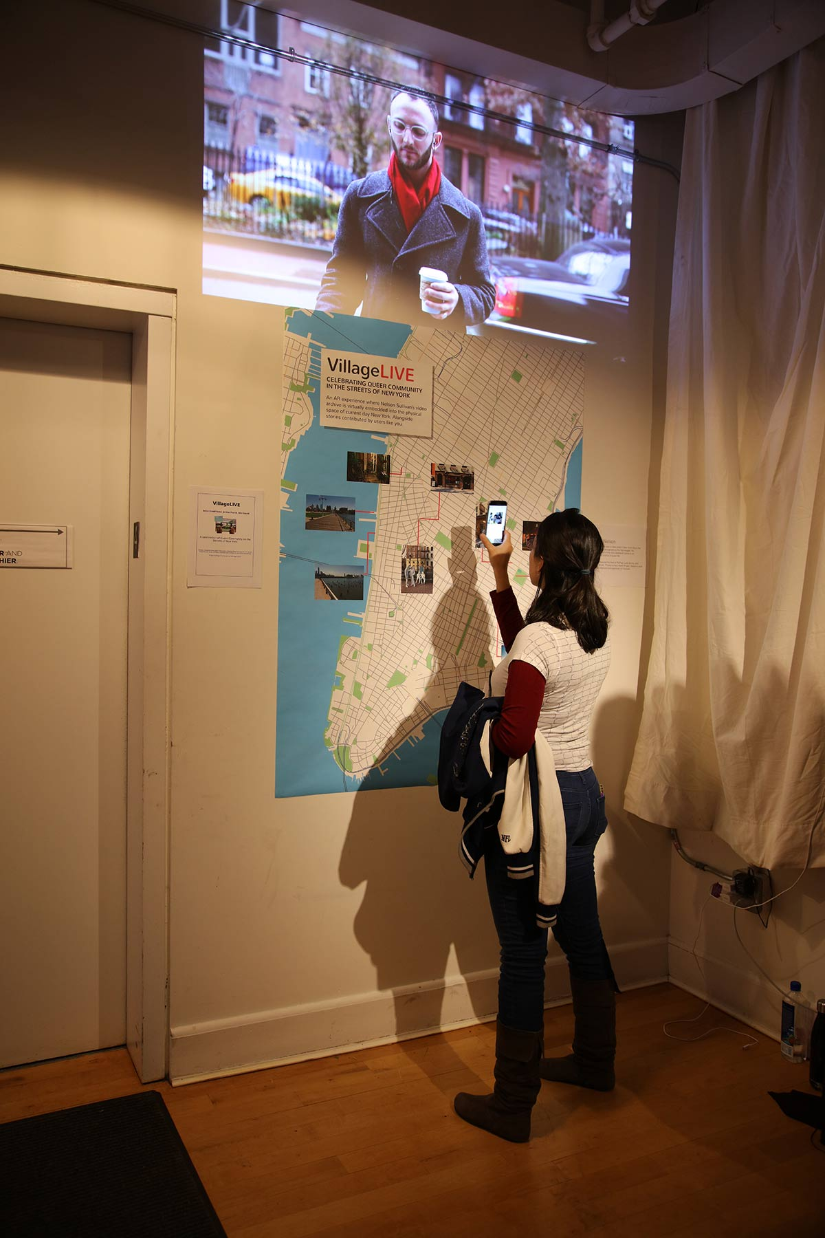 A person with an iphone in front of a map of lower Manhattan, that triggers video footage up above