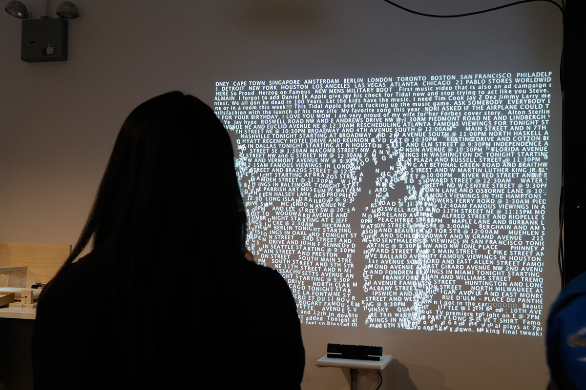 a silhouette of a person looking at a projection filled with words and their shape is disturbing the words
