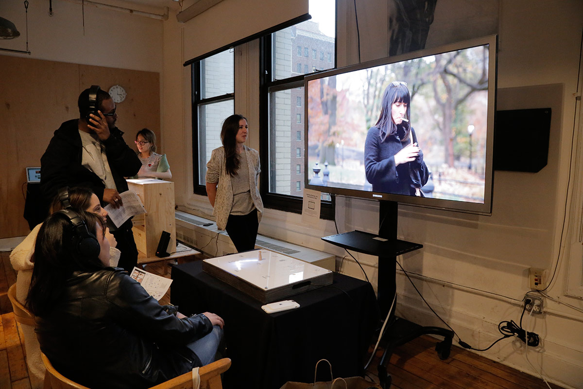 A group of people watching a monitor showing a woman smoking