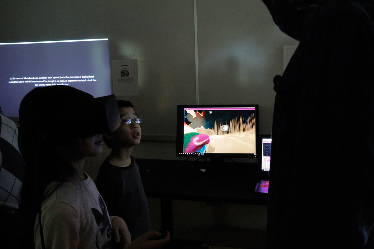 kids wearing VR googles with a monitor showing the landscape they are seeing