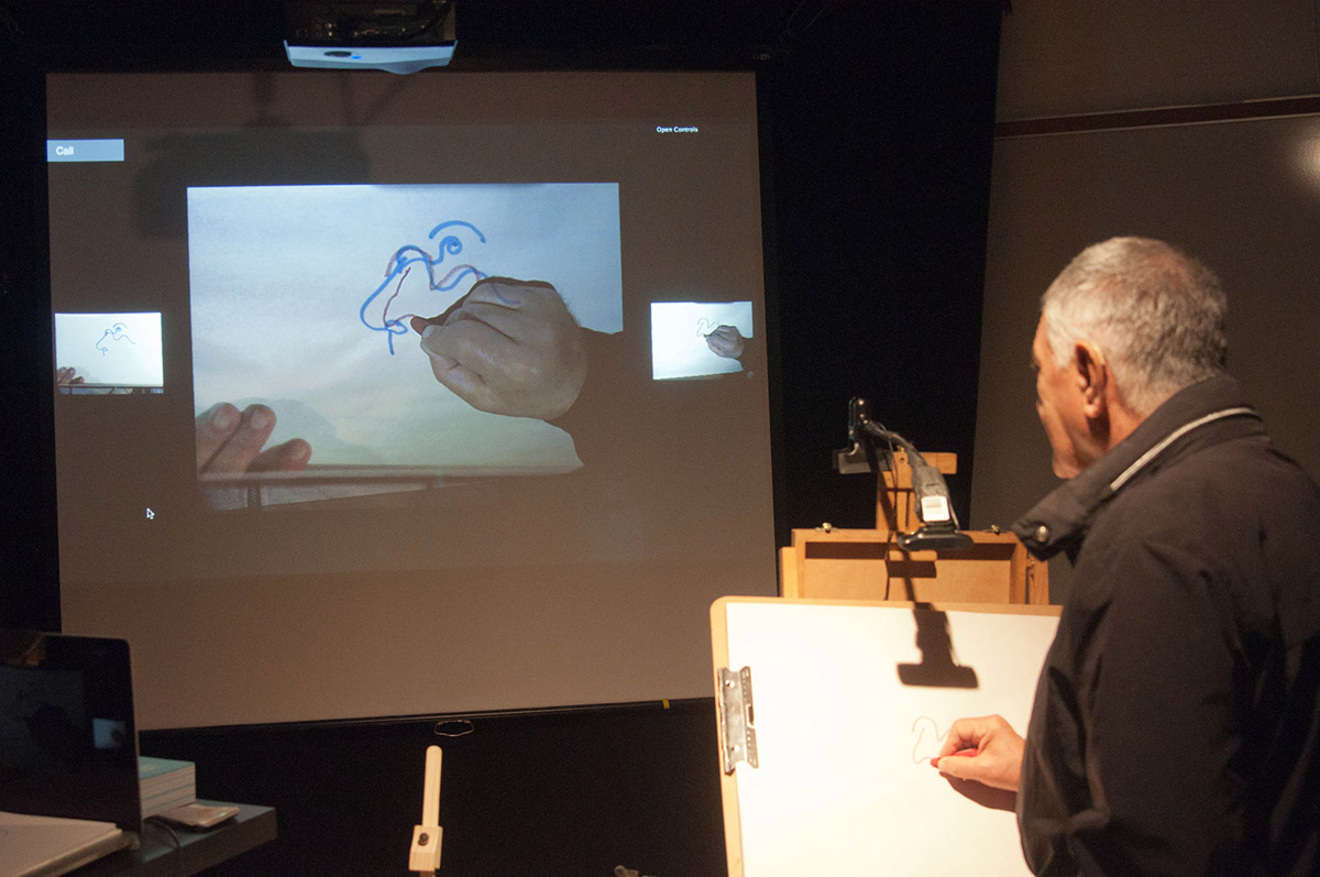 a man drawing on a pad which is projected on a screen with added AR visuals