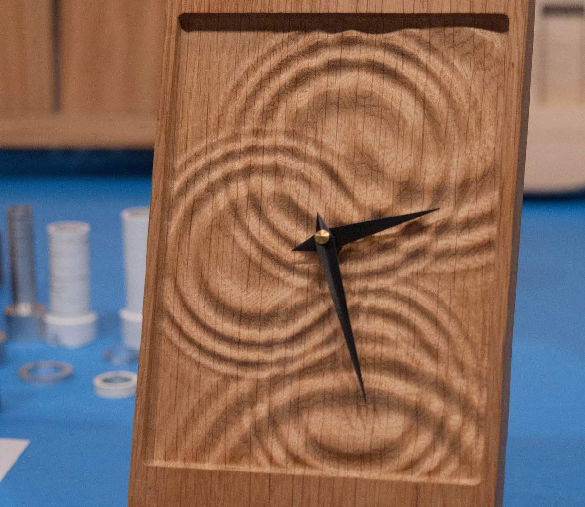 a wooden clock with a ripple design that looks like water drops
