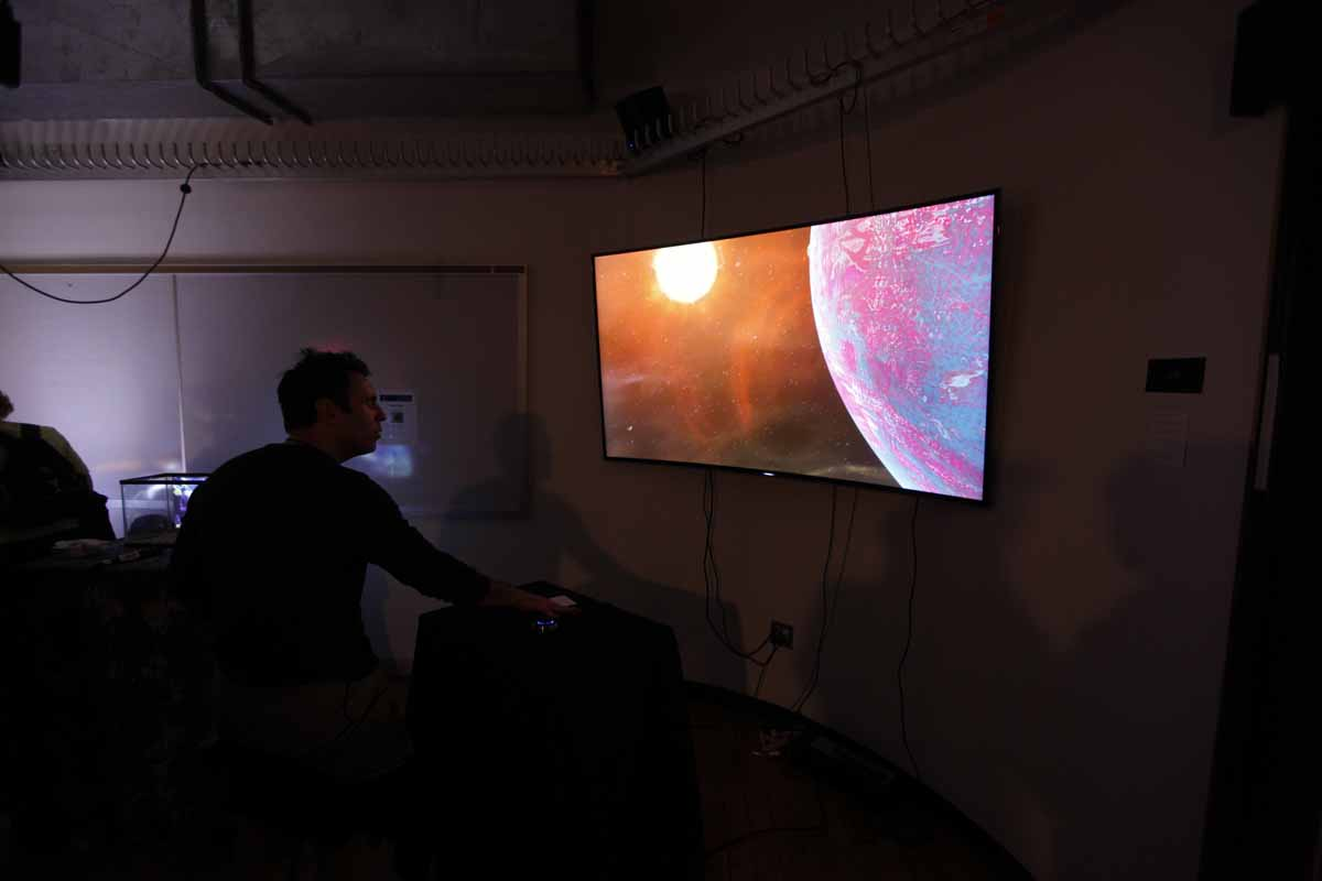 a monitor showing the sun going around a planet