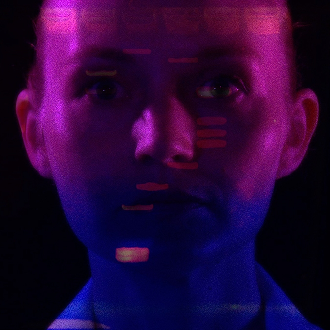 Headshot of Heather Dewey-Hagborg with abstract pink and blue lighting on her face