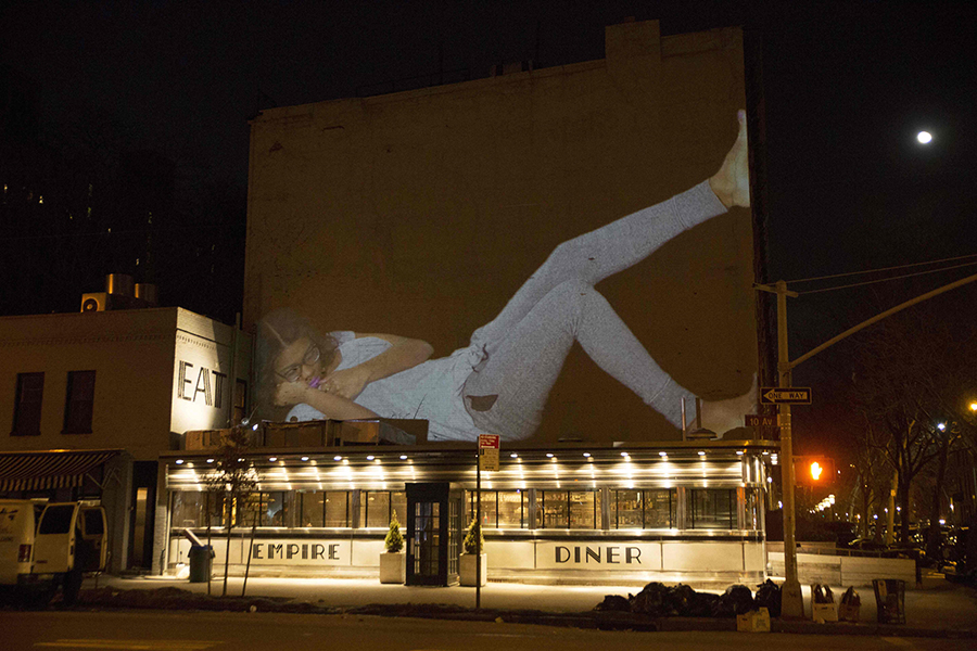 projection of a person napping projected above subway