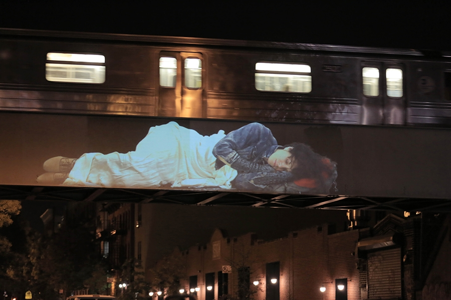 large video projection of person napping above empire diner