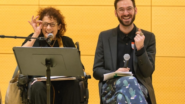 On the left, a white woman in a wheelchair with curly hair adjusts her glasses, smiling. On the right, a bearded white man laughs, mid-snap.