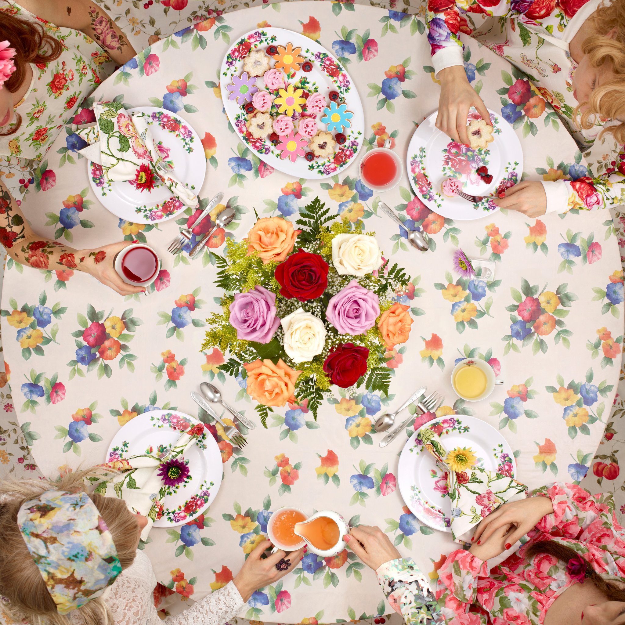 a group of young girls host tea time around a floral tablecloth