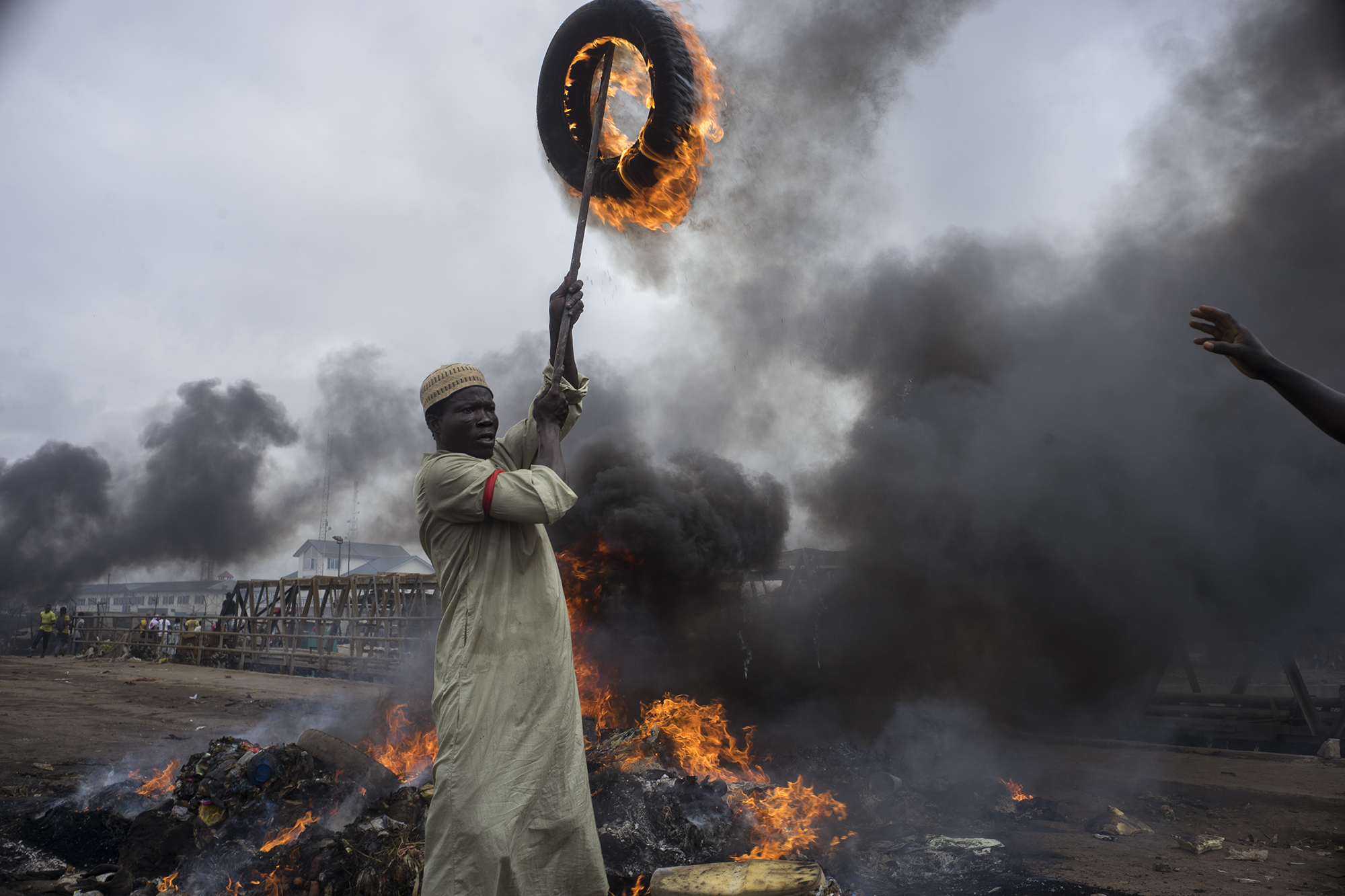 Scene of displaced resident of Agbogbloshie, Accra, Ghana wielding a tire on fire as the landscape burns