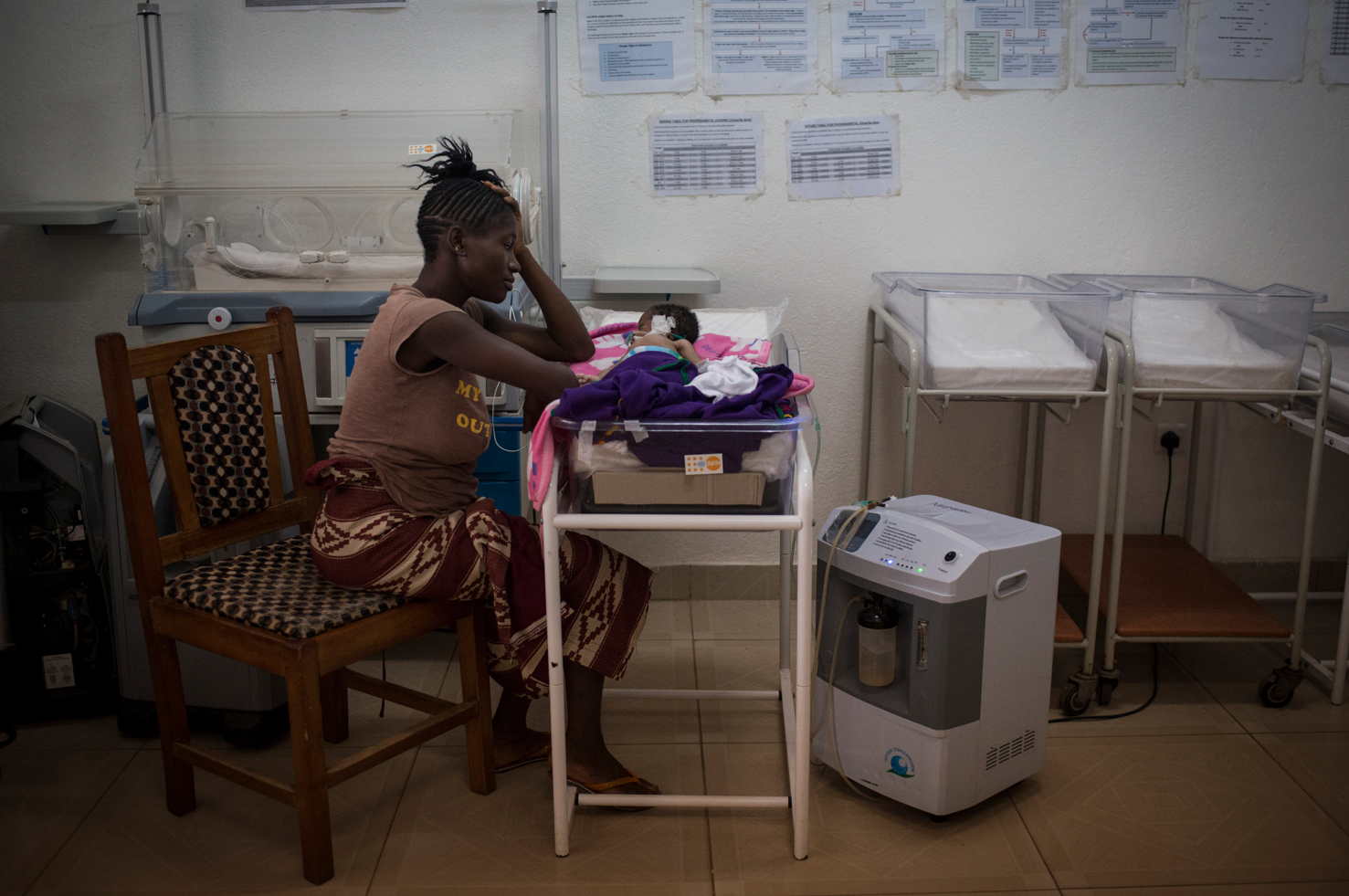 Kema James watching her baby boy in the neonatal intensive care unit three days after giving birth at Kenema Government Hospital in Kenema, Sierra Leone. The baby was born with sepsis and died at five days old. Nov. 12, 2015.