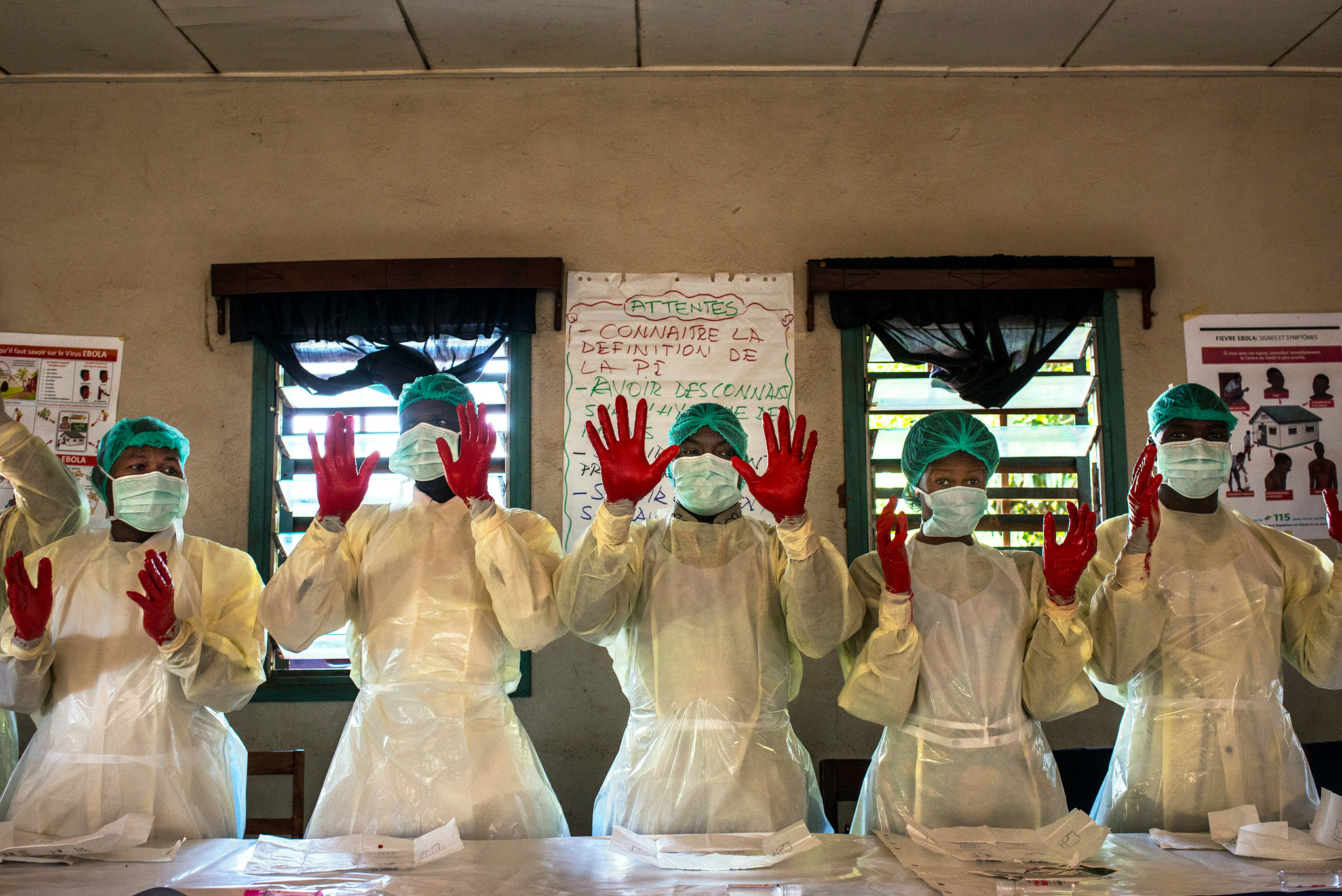 Students at an infection-prevention class showing their results in a hand-washing exercise while wrapped securely in medical robes, masks, and gloves