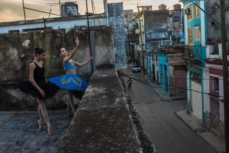 Two girls in ballerina attire practice on a Havana rooftop