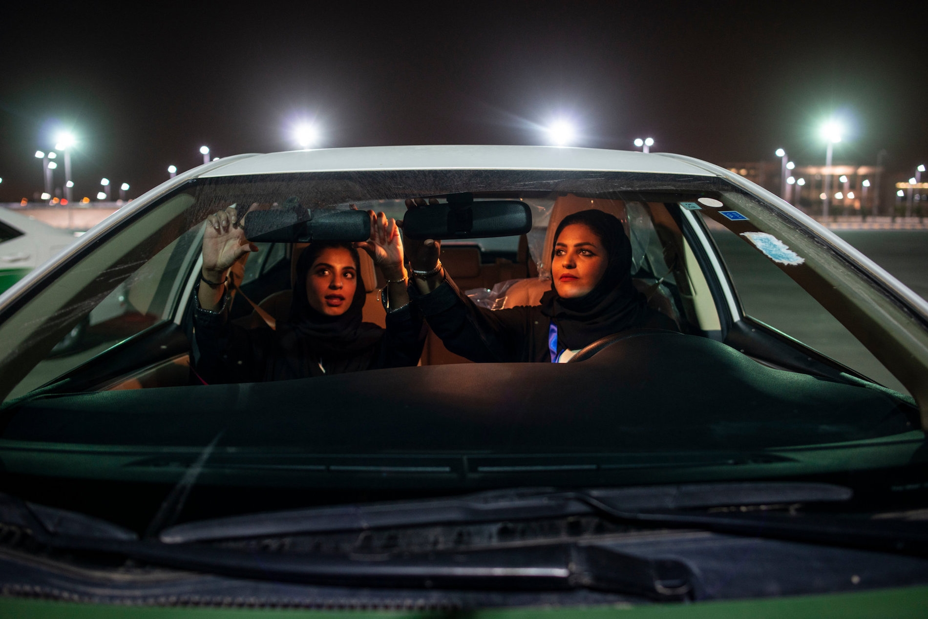 Photo through the front windshield of a car as two Saudi women adjust the mirrors