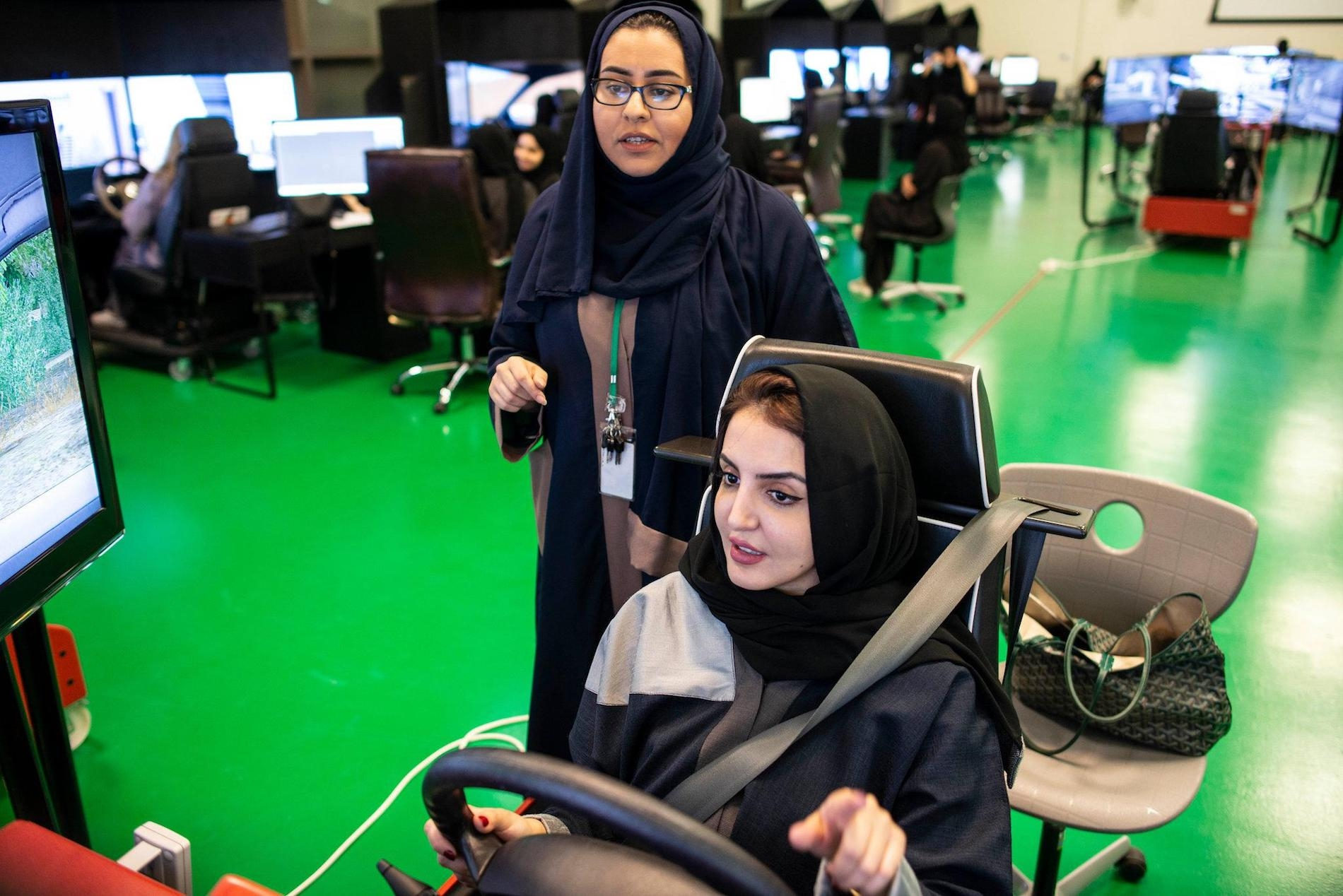 A woman teaches another woman how to drive on a virtual machine.