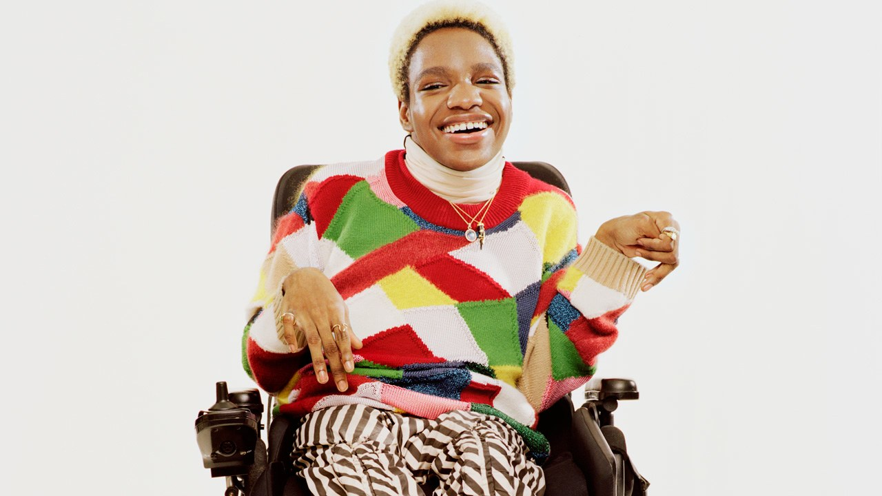 Disabled trans model Aaron Philips smiling in a colorful sweater