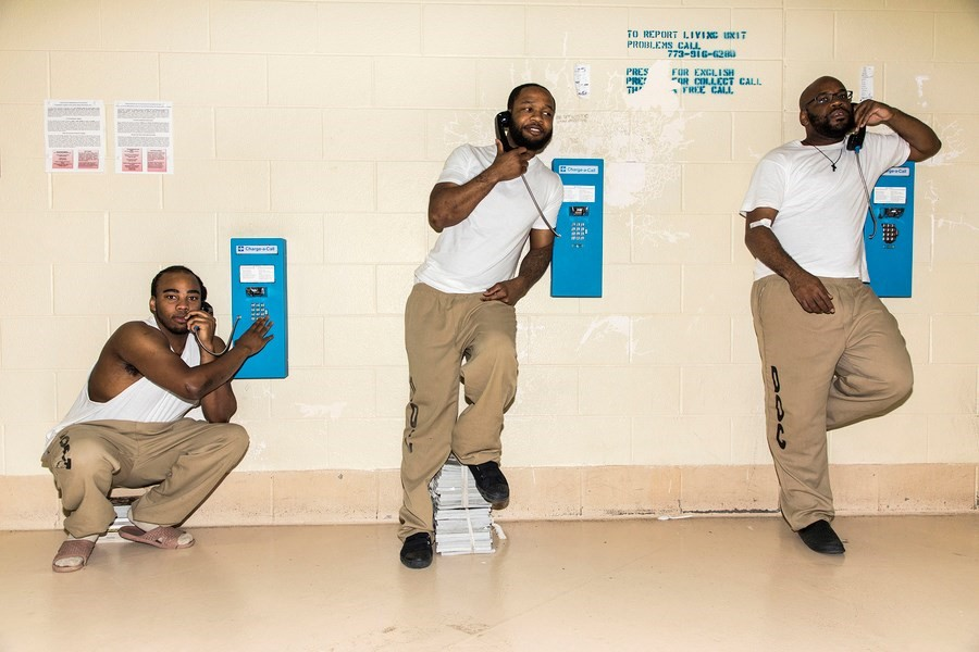 Photo of three men standing at prison pay phones