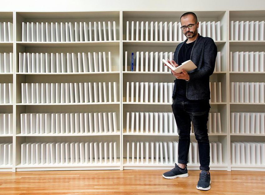 Iraqi-American artist Wafaa Bilal poses with his project 168:01 at the Aga Khan museum, July 17, 2018. Bilal's work is an open appeal to rebuild the Iraqi School of Fine Arts' library, book by book.  (ANDREW FRANCIS WALLACE / TORONTO STAR)