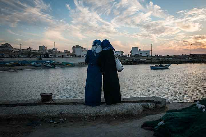 Photo of girls watching the sun set at the harbor in Gaza City