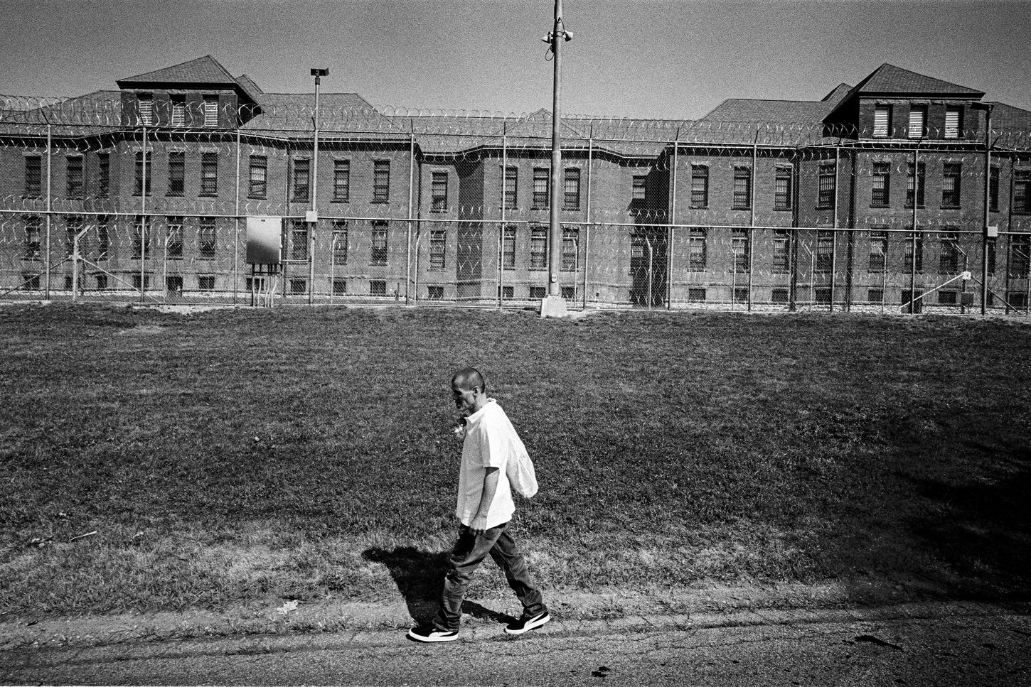 black & white photo of a prisoner walking away from his former place of incarceration, Fishkill Correctional Facility in New York